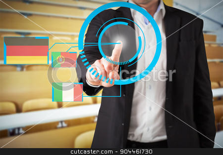 Composite image of businessman standing and pointing stock photo, Businessman standing and pointing against empty seats with tables in a lecture hall by Wavebreak Media