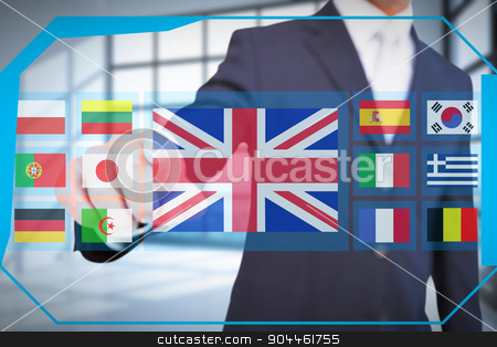 Composite image of smiling businessman in suit pointing  stock photo, Smiling businessman in suit pointing  against room with large windows showing city by Wavebreak Media