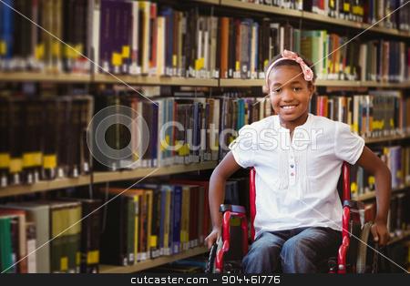 Composite image of girl sitting in wheelchair in school corridor stock photo, Girl sitting in wheelchair in school corridor against close up of a bookshelf by Wavebreak Media