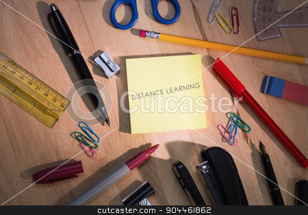 Distance learning against students table with school supplies stock photo, The word distance learning against students table with school supplies by Wavebreak Media