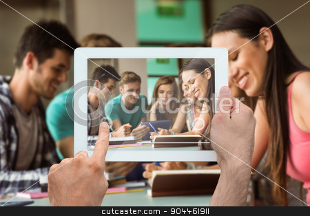 Composite image of hand holding tablet pc stock photo, Hand holding tablet pc against smiling friends sitting studying and using tablet pc  by Wavebreak Media