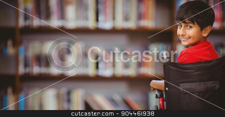 Composite image of boy sitting in wheelchair in school stock photo, Boy sitting in wheelchair in school against library shelf by Wavebreak Media