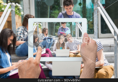 Composite image of hand holding tablet pc stock photo, Hand holding tablet pc against students sitting on steps studying by Wavebreak Media