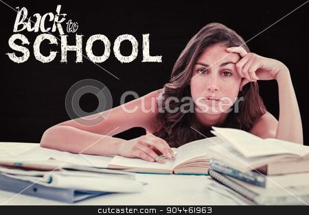 Composite image of bored student doing her homework stock photo, Bored student doing her homework against black by Wavebreak Media