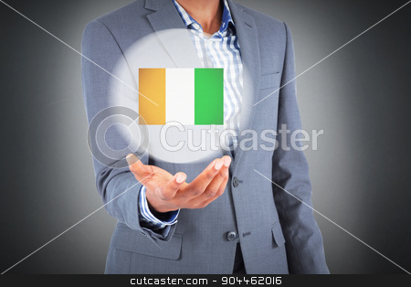 Composite image of businessman holding hand out stock photo, Businessman holding hand out against grey background by Wavebreak Media