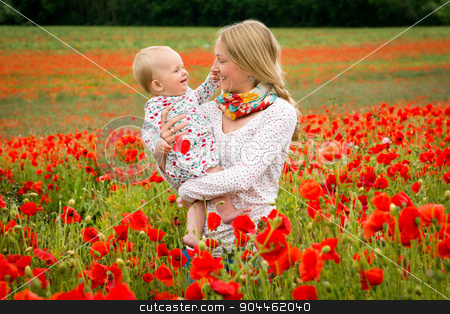 Mommy and daughter in a meadow stock photo, Young mother and her daughter having fun in a meadow full of poppy flowers during a sunny afternoon by Kamila Starzycka