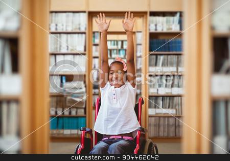 Composite image of girl in wheelchair in school corridor stock photo, Girl in wheelchair in school corridor against library by Wavebreak Media