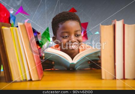 Composite image of cute boy reading book in library stock photo, Cute boy reading book in library against geometric design by Wavebreak Media