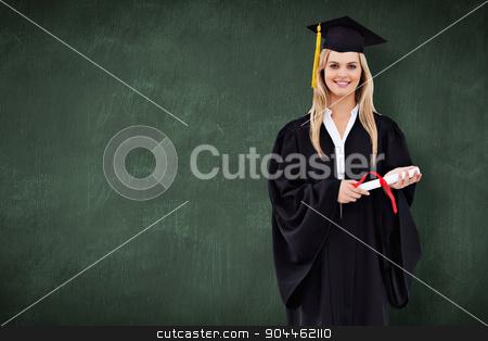 Composite image of smiling blonde student in graduate robe holdi stock photo, Smiling blonde student in graduate robe holding her diploma against green chalkboard by Wavebreak Media