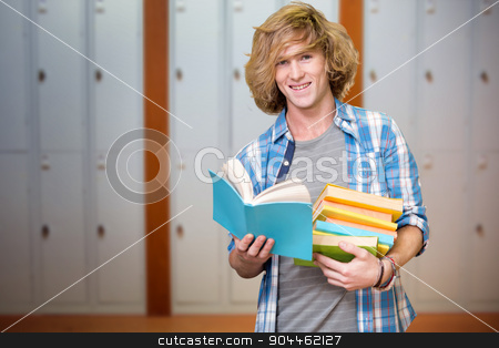 Composite image of student reading book stock photo, Student reading book against closed lockers in a row at the college by Wavebreak Media