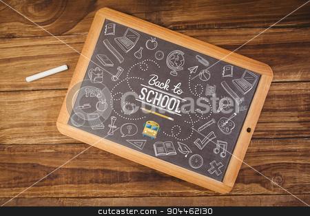 Composite image of back to school stock photo, back to school against chalkboard on desk by Wavebreak Media