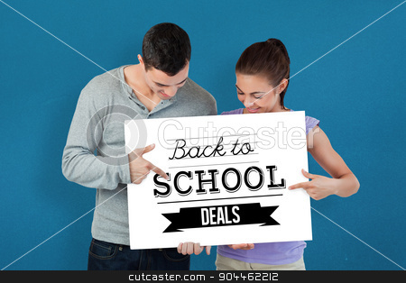 Composite image of young couple pointing at banner they are pres stock photo, Young couple pointing at banner they are presenting against blue background by Wavebreak Media