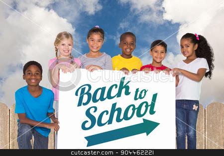 Composite image of elementary pupils showing card stock photo, Elementary pupils showing card against fence under blue sky by Wavebreak Media