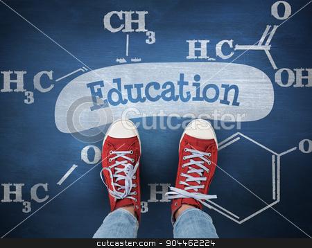 Education against blue chalkboard stock photo, The word education and casual shoes against blue chalkboard by Wavebreak Media