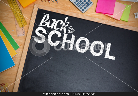 Composite image of back to school stock photo, back to school against chalkboard on desk by Wavebreak Media
