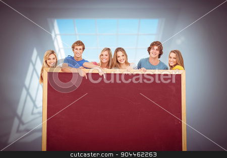 Composite image of smiling group of people with a blank space as stock photo, Smiling group of people with a blank space as they point to it against room with large windows by Wavebreak Media