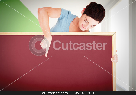 Composite image of brunette pointing at a blank panel stock photo, Brunette pointing at a blank panel against modern white and green room with window by Wavebreak Media