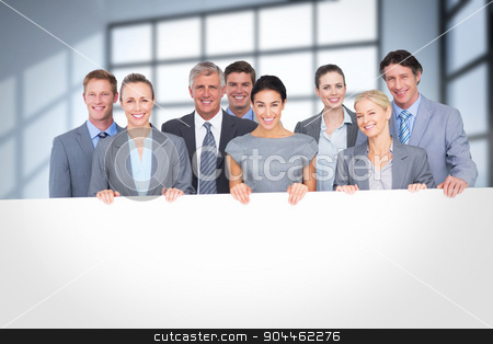 Composite image of smiling business team holding poster stock photo, Smiling business team holding poster against room with large windows showing city by Wavebreak Media