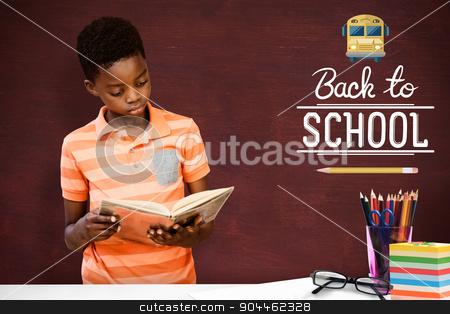 Composite image of cute boy reading book in library stock photo, Cute boy reading book in library against desk by Wavebreak Media