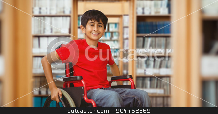 Composite image of portrait of boy sitting in wheelchair stock photo, Portrait of boy sitting in wheelchair against library by Wavebreak Media