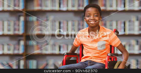 Composite image of portrait of boy sitting in wheelchair at libr stock photo, Portrait of boy sitting in wheelchair at library against library shelf by Wavebreak Media