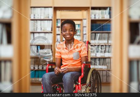 Composite image of full length portrait of happy boy on wheelcha stock photo, Full length portrait of happy boy on wheelchair against library by Wavebreak Media