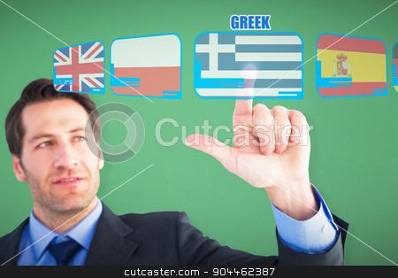 Composite image of confident businessman pointing at something stock photo, Confident businessman pointing at something against green by Wavebreak Media