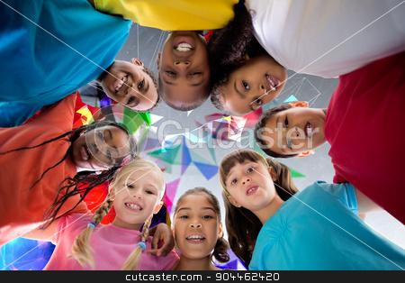 Composite image of elementary pupils smiling stock photo, Elementary pupils smiling against geometric design by Wavebreak Media