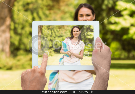 Composite image of hand holding tablet pc stock photo, Hand holding tablet pc against portrait of an university student holding book  by Wavebreak Media