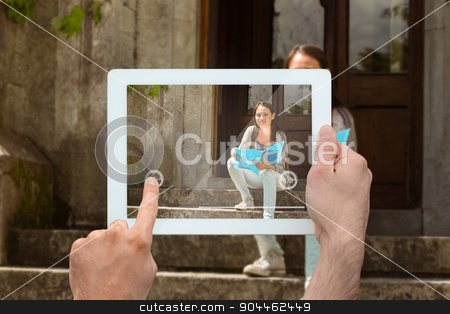 Composite image of hand holding tablet pc stock photo, Hand holding tablet pc against smiling student sitting and holding book by Wavebreak Media