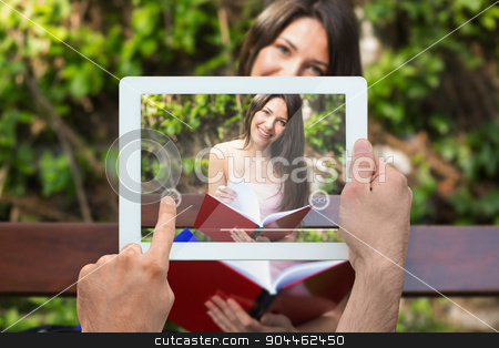 Composite image of hand holding tablet pc stock photo, Hand holding tablet pc against pretty student studying outside on campus by Wavebreak Media