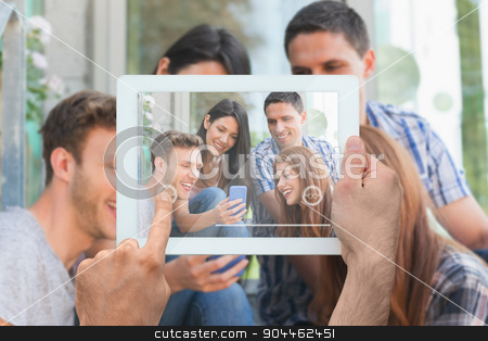 Composite image of hand holding tablet pc stock photo, Hand holding tablet pc against happy students looking at smartphone outside on campus by Wavebreak Media