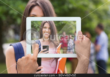 Composite image of hand holding tablet pc stock photo, Hand holding tablet pc against pretty student sending a text outside on campus by Wavebreak Media