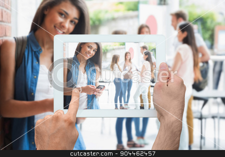 Composite image of hand holding tablet pc stock photo, Hand holding tablet pc against pretty student smiling at camera with classmates behind by Wavebreak Media