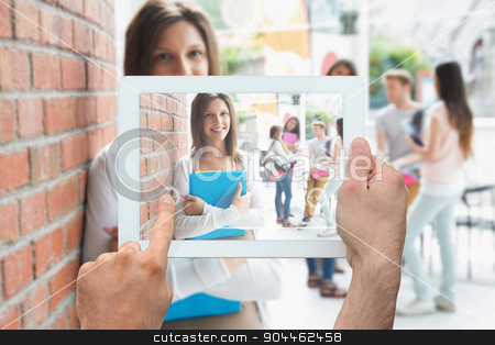 Composite image of hand holding tablet pc stock photo, Hand holding tablet pc against pretty student smiling and holding notepads by Wavebreak Media