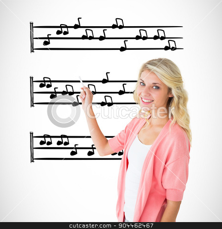 Composite image of young pretty student writing with chalk stock photo, Young pretty student writing with chalk against music notes by Wavebreak Media
