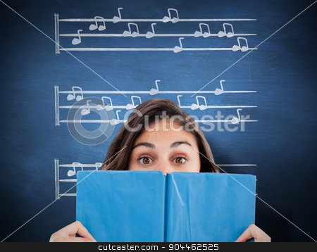 Composite image of portrait of a student hiding behind a blue bo stock photo, Portrait of a student hiding behind a blue book against blue chalkboard by Wavebreak Media