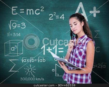 Composite image of pretty brunette looking at notebook  stock photo, Pretty brunette looking at notebook  against green chalkboard by Wavebreak Media