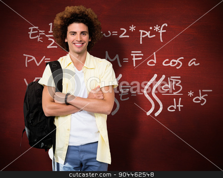 Composite image of young man with arms crossed in office corrido stock photo, Young man with arms crossed in office corridor against desk by Wavebreak Media
