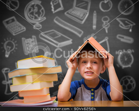 Composite image of cute boy with book on head stock photo, Cute boy with book on head against black background by Wavebreak Media
