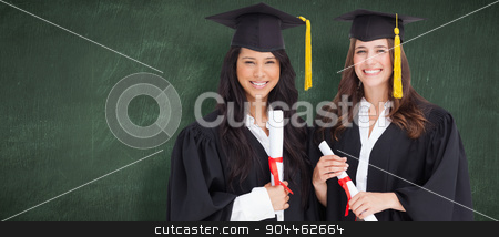 Composite image of two friends stand together after graduating stock photo, Two friends stand together after graduating against green chalkboard by Wavebreak Media