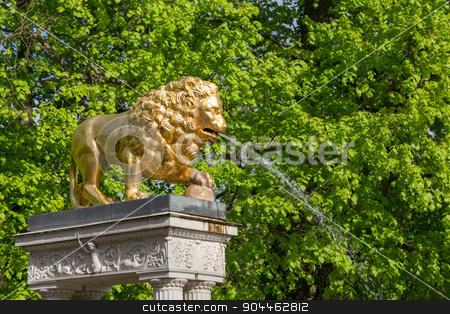 Lion fountain stock photo, A golden lion gargoyles on a pedestal at the fountain by Bernd Kröger