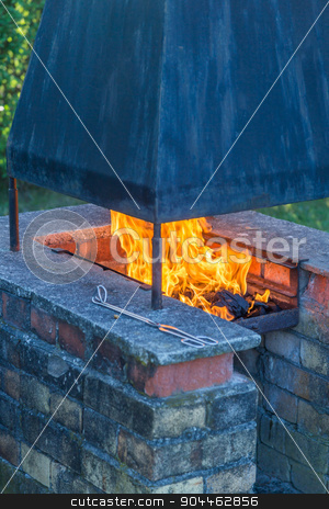 Garden fireplace and barbecue stock photo, Open fire in the barbecue grill with smoke extractor and steel by Bernd Kröger