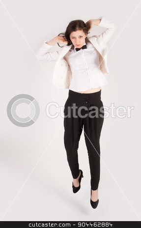 Jumping business woman stock photo, Jumping young attractive business woman in white jacket by Aikon