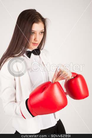 young businesswoman in boxing gloves stock photo, Smiling business lady with red gloves holding cash at white background by Aikon