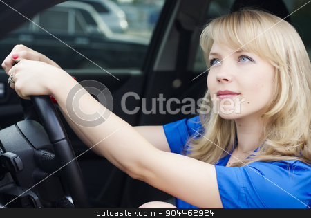 Young woman in a car stock photo, Young woman sitting in a car and driving by Aikon