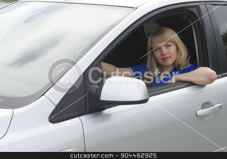 Young woman in car stock photo, Young woman sitting in a car and driving by Aikon