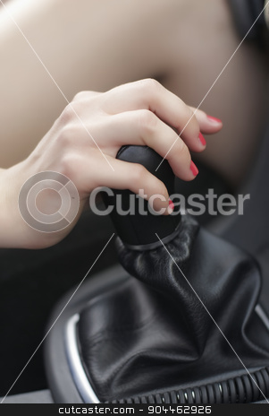 Driving girl stock photo, Girl switching speed by lever in car by Aikon