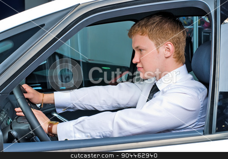 Driving man stock photo, Young man driving car in relaxed position by Aikon