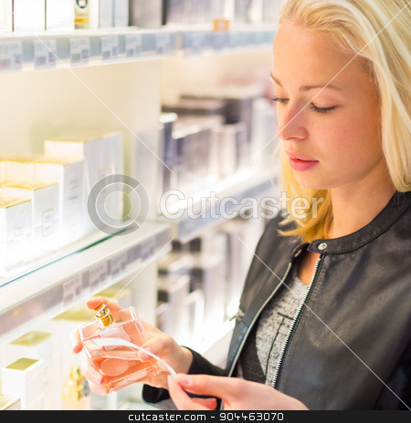 Beautiful woman shopping in beauty store. stock photo, Casual blond young woman smelling perfume in retail store. Beautiful blond lady testing  and buying cosmetics in a beauty store. by kasto